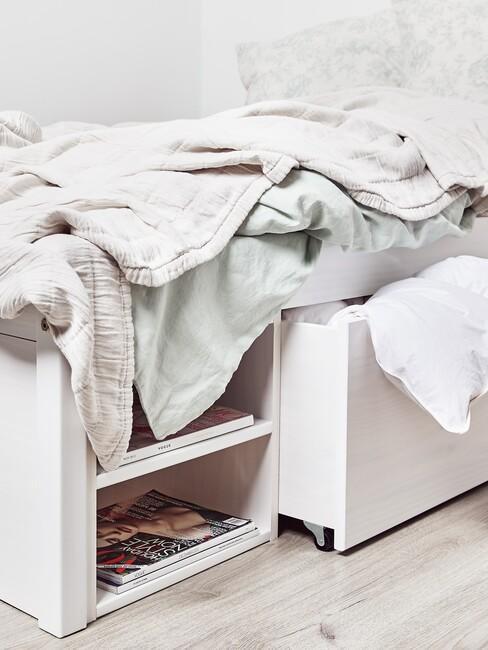 wit bed met vakken onder het bed en groene lakens