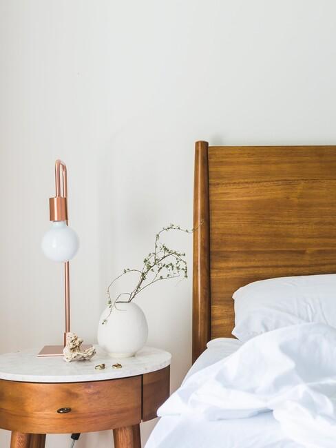 houten hoofdbord met houten nachtkastje en gouden lamp