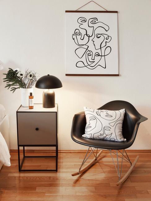grijze nachtkastje met zwarte stoel en wit kussen