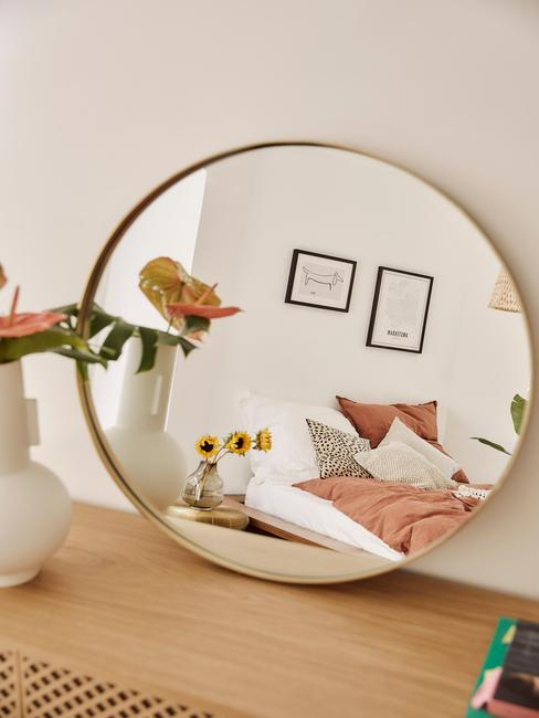 gouden ronde spiegel op houten kast