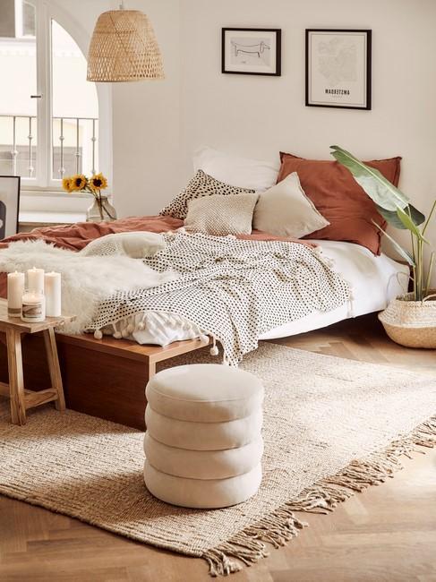 houten bed met panter deken en toupe poef