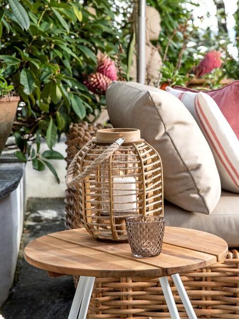 rieten lampioen met kaars op houten tafel met witte posten