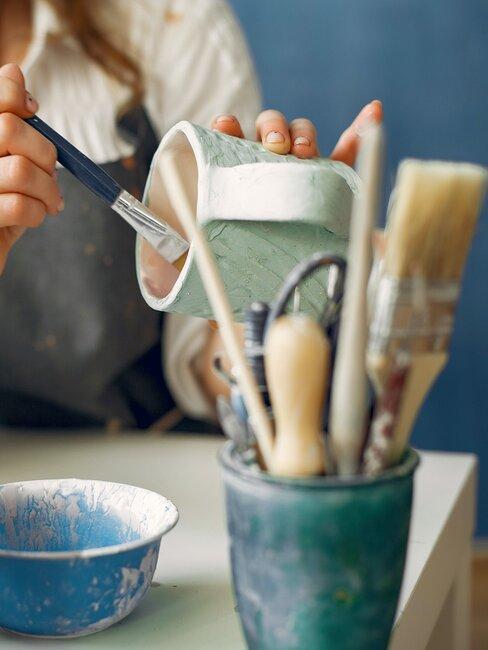 vrouw beschildert porseleinen mok