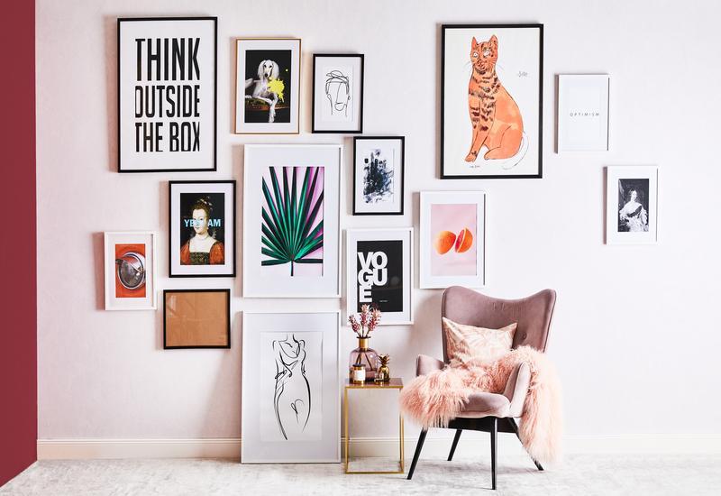 fotolijsten op roze muur met roze stoel en zachte roze deken