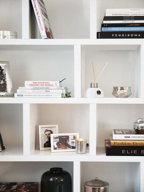 witte boekenkast met fotolijstjes en boeken