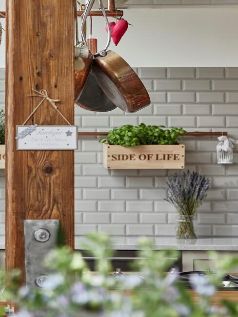 keuken met witte tegels en houten plantenbak tegen de muur