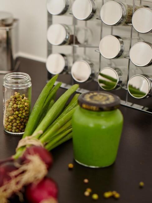 kruidenpotjes in een rek met groenten en kruiden op de aanrecht
