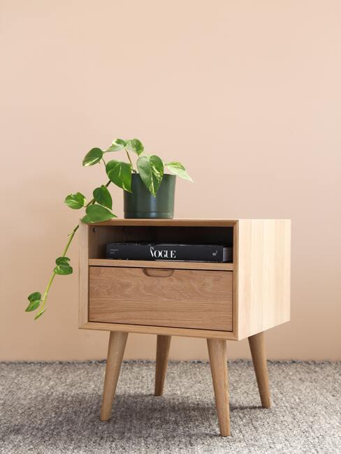 houten nachtkastje met plant en zalmroze muur