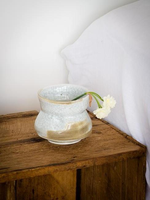 houten nachtkastje met witte vaas
