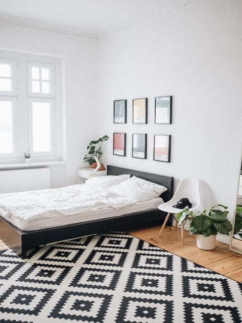 wit met zwart kleeden witte stoel bij een houten bed