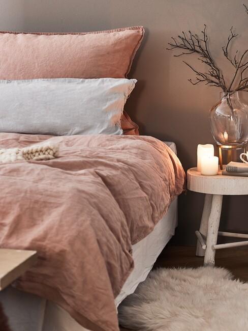 roze dekbed met houten nachtkastje