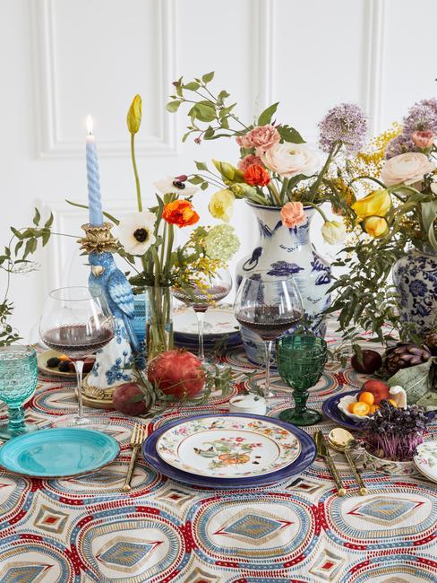 Bont gedekte tafel met Porseleinen servies, kaarsen en bloemen