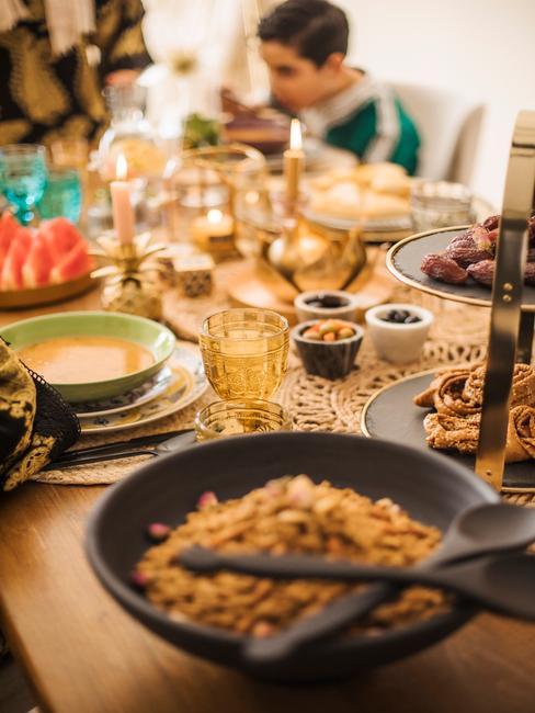 zwarte kom met eten en een gedekte tafel