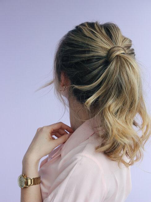 Blonde vrouw met lage paardenstaart met een pluk haar eromheen gedraaid