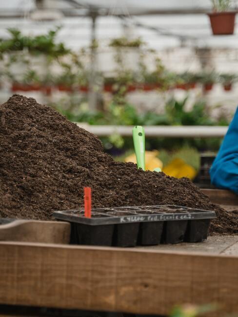 zwarte plantenpotten met compost
