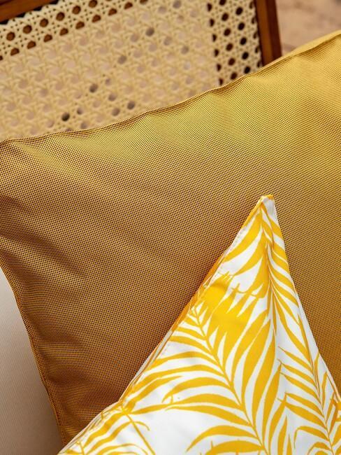 gele kussens op een rieten tuinstoel