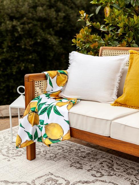 houten buitenbank met gele en witte kussens