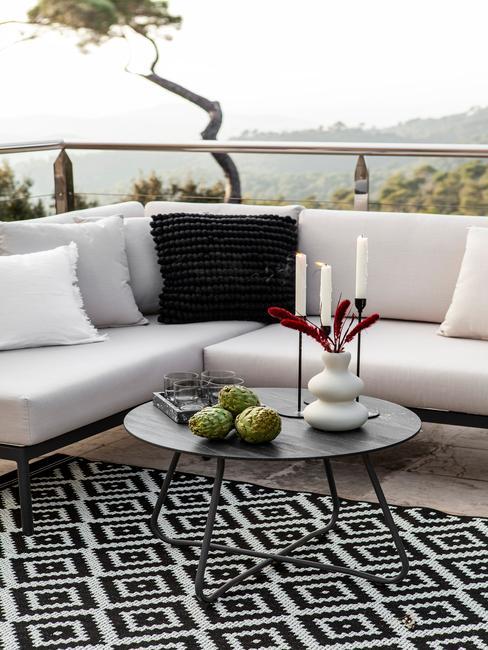 witte outdoor loungebank met zwarte en witte kussen en een outdoor vloerkleed