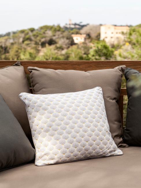 beige en witte kussens op een outdoor bank