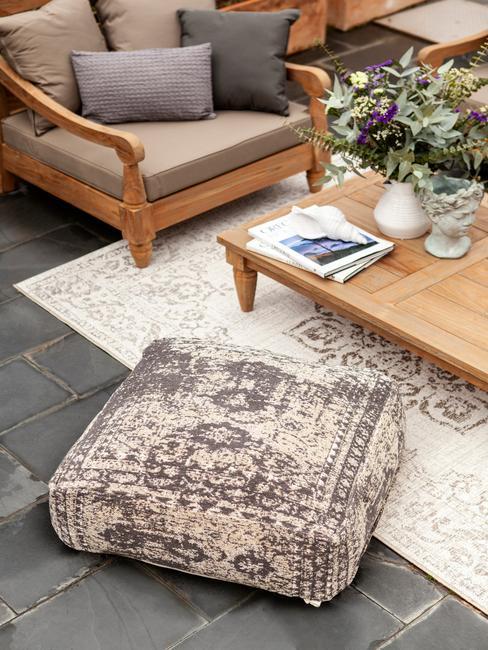 houten tafel en bank met grijze kussens