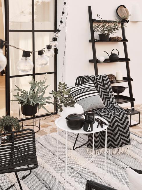 zwarte trapladder met zwarte stoelen en witte tafel