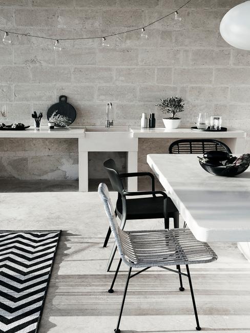 witte tafel met zwarte en witte tuinstoelen