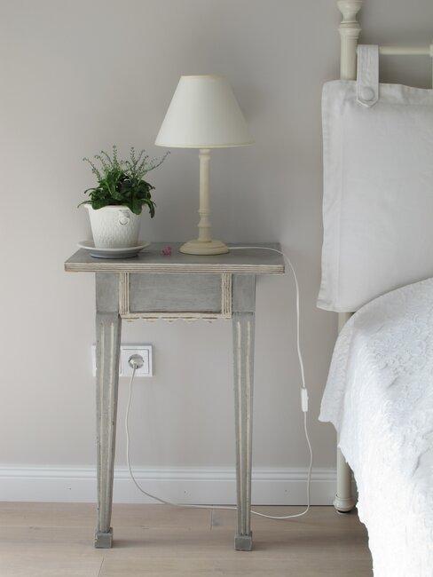grijs nachtkastje met witte lamp