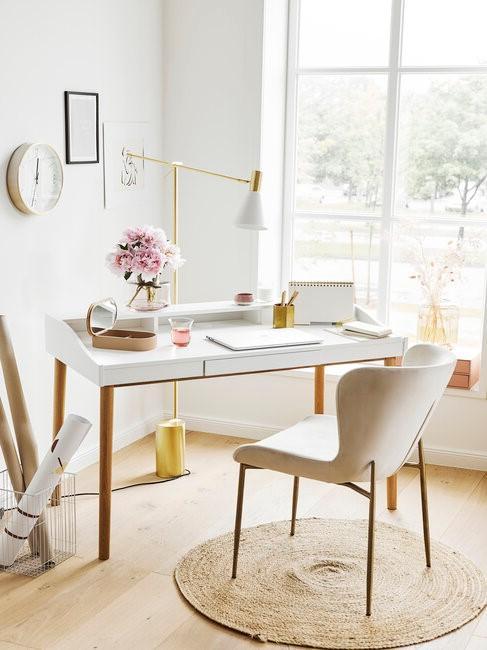 wit bureau met roze bloemen en een gouden lamp