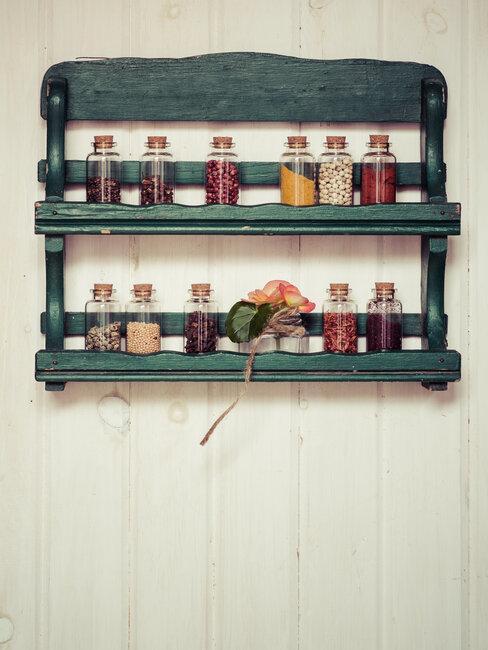 groen houten kruidenrek bevestigd aan de muur met kruidenpotjes