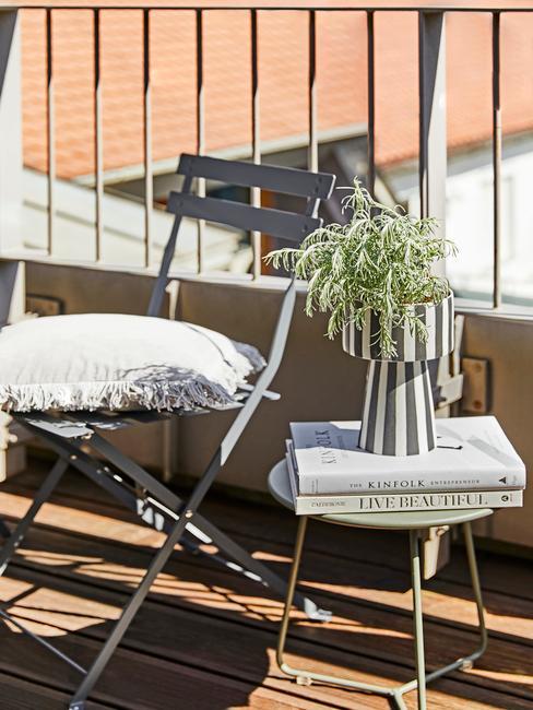 grijze stoel met wit kussen en een plantenpot