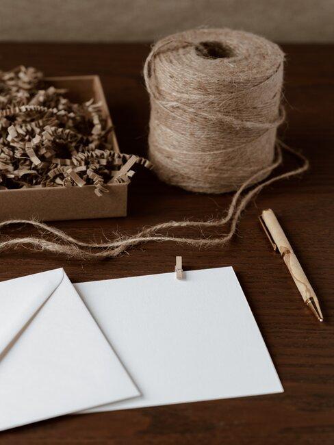 garen en een envelop op een houten dressoir
