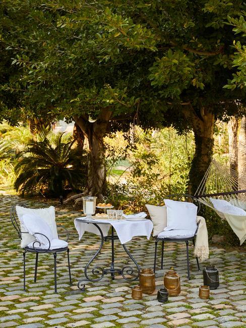 bomen in een tuin met een stalen tuinset met witte kussens