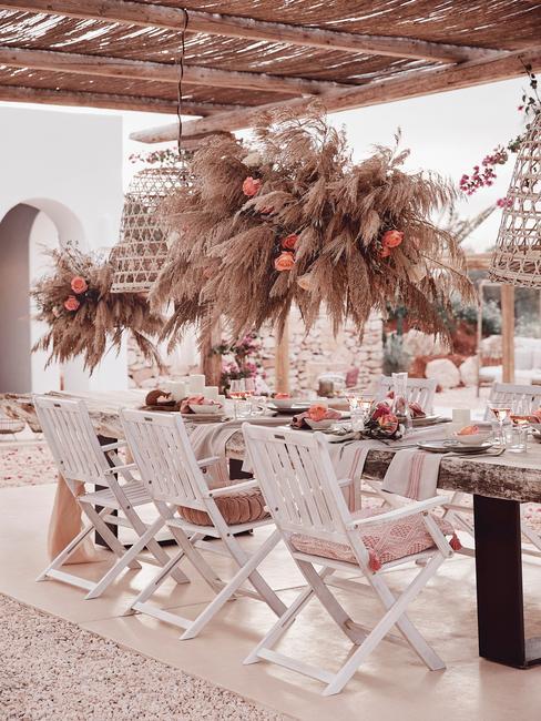 witte stoelen met houten tafel onder een pergola