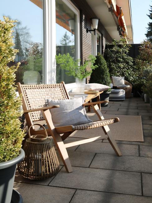 houten stoel met wit kussen en zwarte plantenpot
