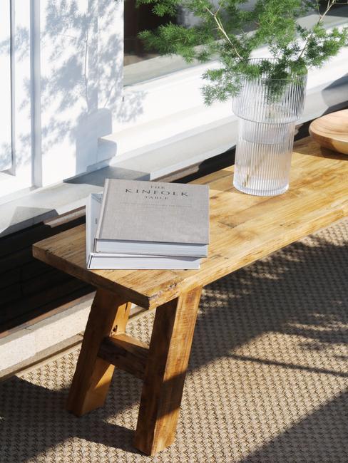 houten tafel met witte boeken met glazen vaas