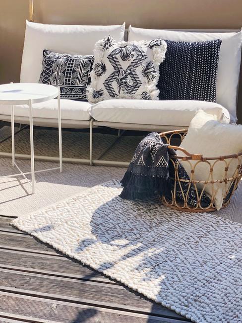 toupe bank met gekleurde kussens en wit bijzettafel