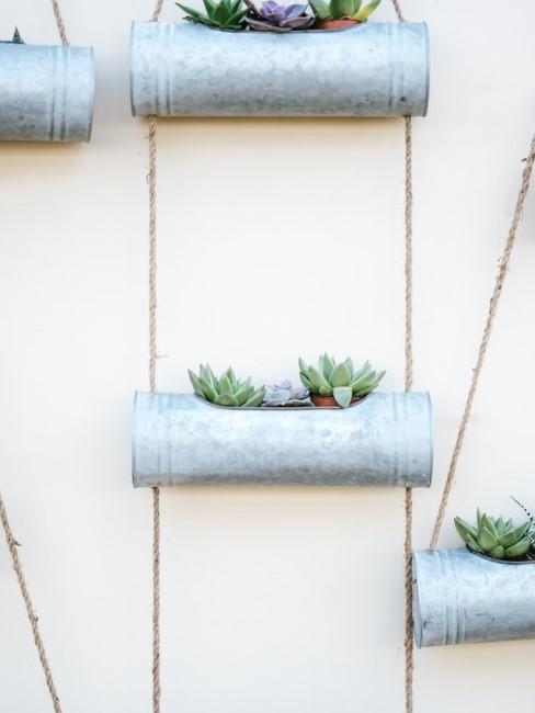 schutting ideeën: zilveren plantenpotten aan touwen