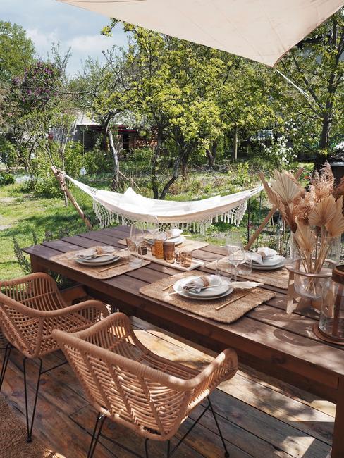 achtertuin ideeën: rieten stoelen met houten tafel