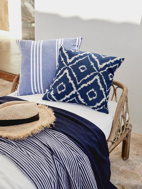blauwe kussens op rieten ligbed