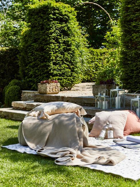 grijs buiten zitkussen met roze kussens in een natuurlijke tuin