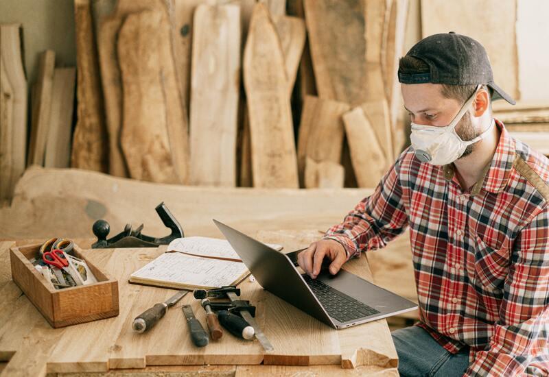 man aan houten tafel op laptop met gereedschap