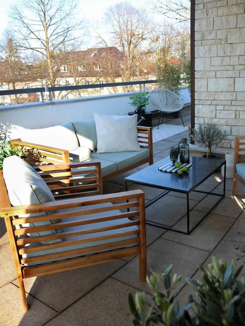 houten stoelen met witte kussens en zwarte bijzettafel