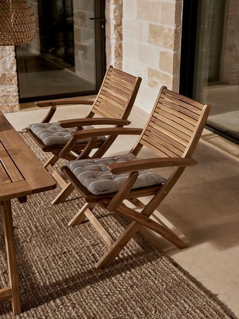 terras met houten stoelen met grijze kussens en rieten kleed