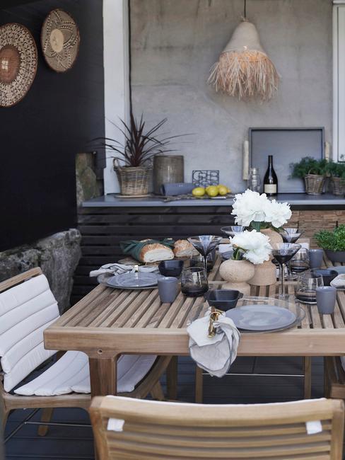 houten tuinset met witte kussens en grijs servies