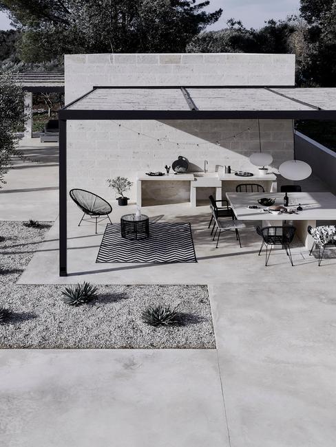 witte buitenkeuken met witte tafel en zwarte stoelen