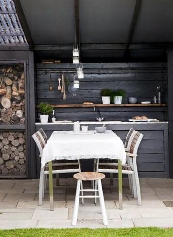 donker grijze buitenkeuken met houten tafelset