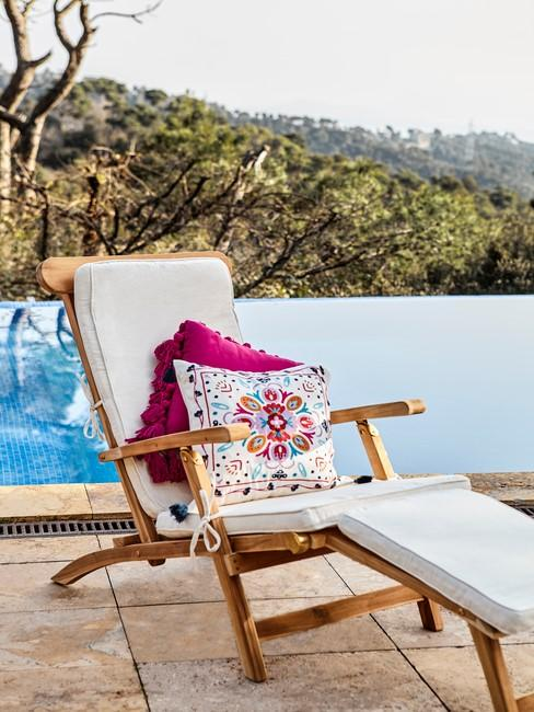 houten ligstoel met witte en gekleurde kussens