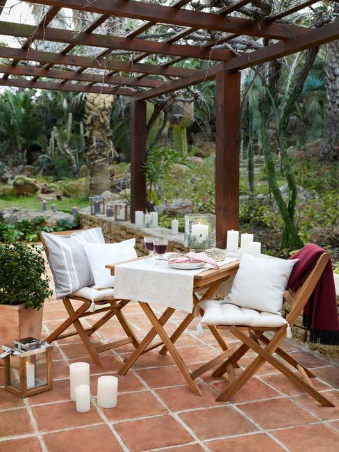 houten tuinset met witte kussens en terracotta tegels