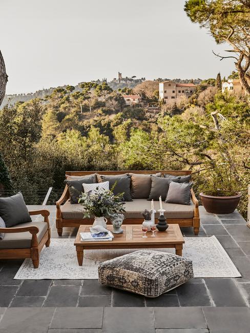 houten set met grijze kussens op een terras van grijze tegels in de tuin