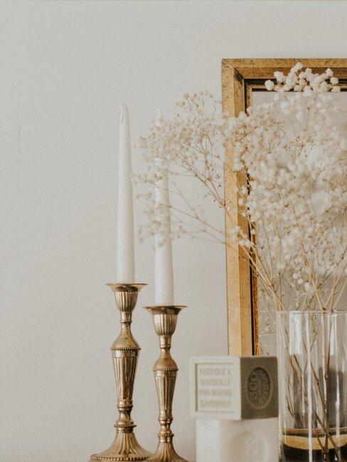 gipskruid in transparante vaas met twee kandelaars en houten lijst